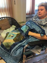 Youville resident Maria enjoying one of the handmade quilts.