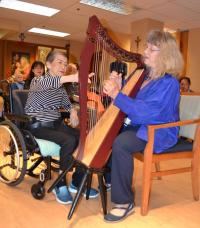 Holy Family Hospital resident Emilia Laurea plucks the strings of a new harp with music therapist Gabriele Clement.